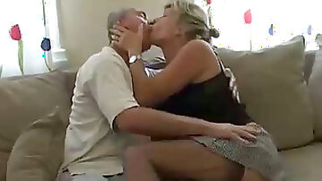 Mature white man and his blonde cougar partner on the couch